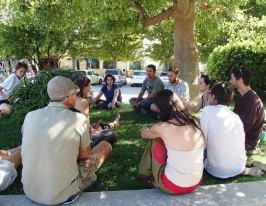 Em Port-Bou, um dos 4 grupos de discussão, sob uma árvore na praça central, aprendendo sobre o funcionamento das tais Cooperativas Integrais.